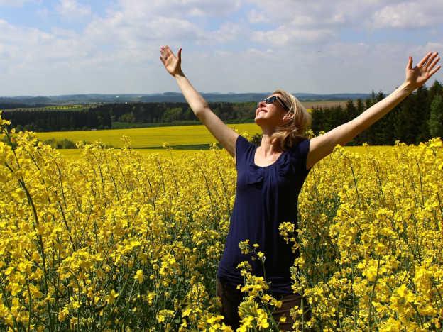 Frau auf Blumenfeld ist voller Dankbarkeit zu Gott